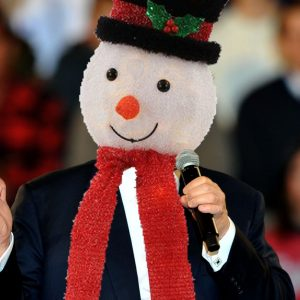 image of Donald Trump holding a microphone in his left hand and gesturing with the other. A primitively rendered snowman's head and scarf are superimposed where the president's head and red tie would be.
