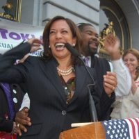 2010 photo of Kamala Harris laughing while standing behind a podium at a rally in San Francisco