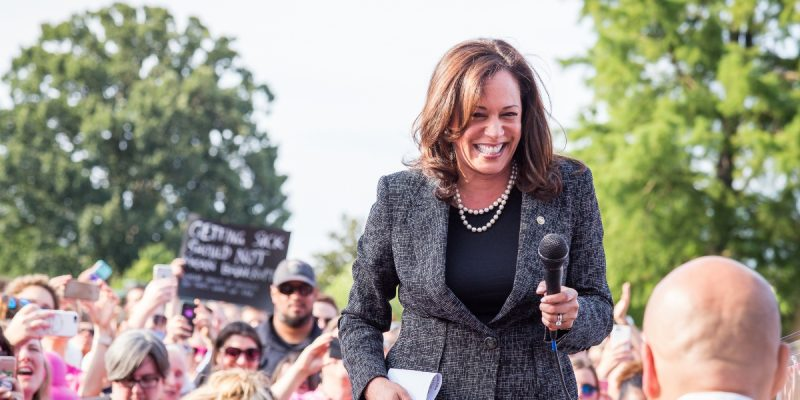 A smiling Kamala Harris at a summertime political rally, handing a microphone to fellow U.S. Sen. Cory Booker, who is visible only by the back of his bald head