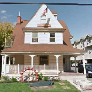 Photo of the former home of the Theta Tau fraternity house, a three-story residence on a small lot near the campus of Syracuse University in Syracuse, New York