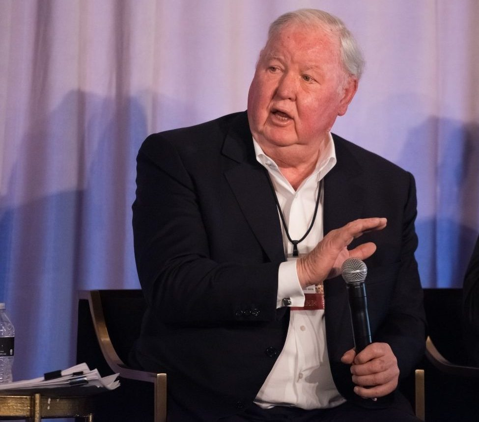 Jim Larkin at Reason Weekend 2019, seated in an armchair in an Arizona Biltmore event suite, gesturing with his right hand while speaking into a wireless microphone held in his left