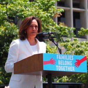 Kamala Harris speaking outside before a podium.