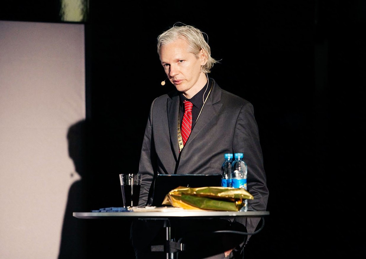 Julian Assange in suit and tie at a lectern, speaking.