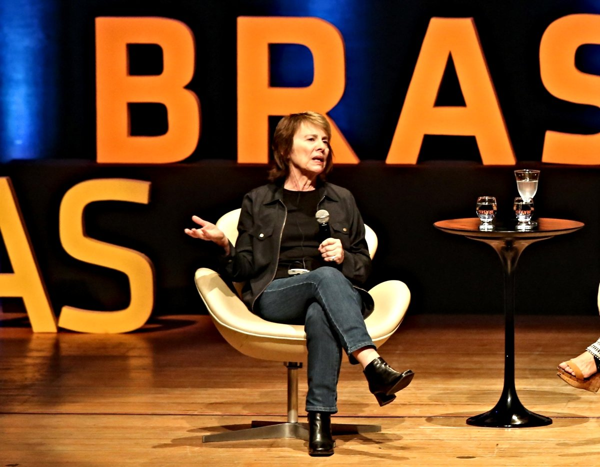An image of Camille Paglia speaking at a conference in Bazil.