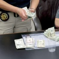 Photo of a cop counting cash.